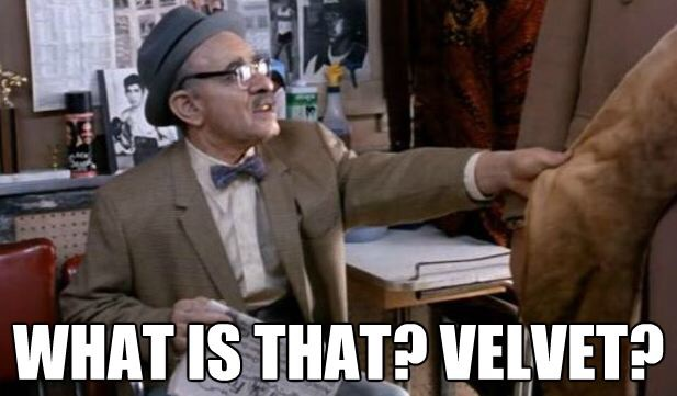"Meme of Eddie Murphy's character Saul in film Coming to America stroking lion fur coat saying ""What is that? Velvet?"""